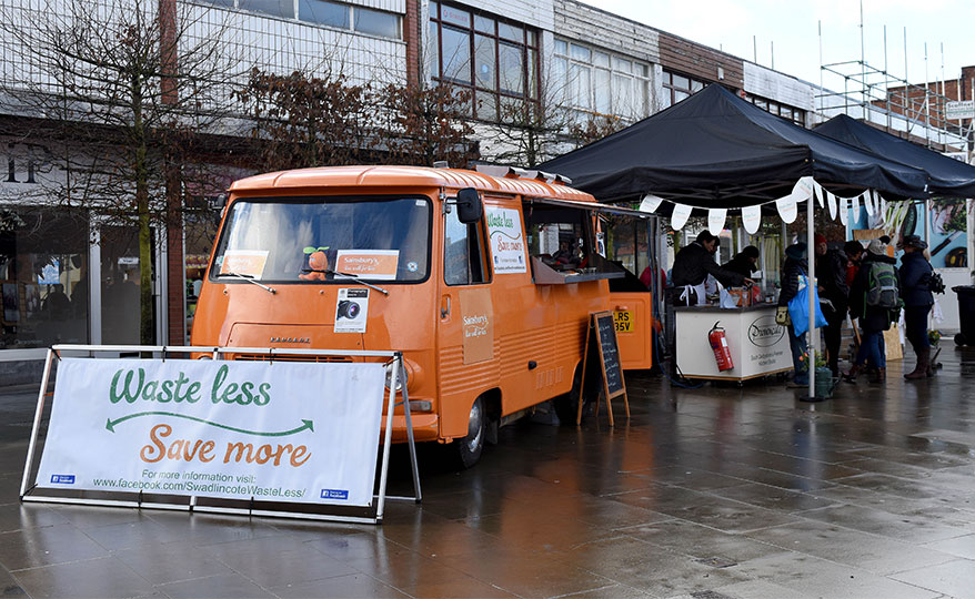 Waste less, Save more banner leaning against an orange Sainsbury's campervan.